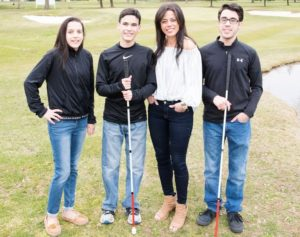 Kristin and her hildren standing on grass.  Both boys are holding their canes
