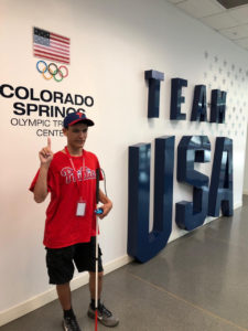 Mitchellinfront of the  Oympic Training Center  Logo and TEAM USA  onthe wall b ehind him.