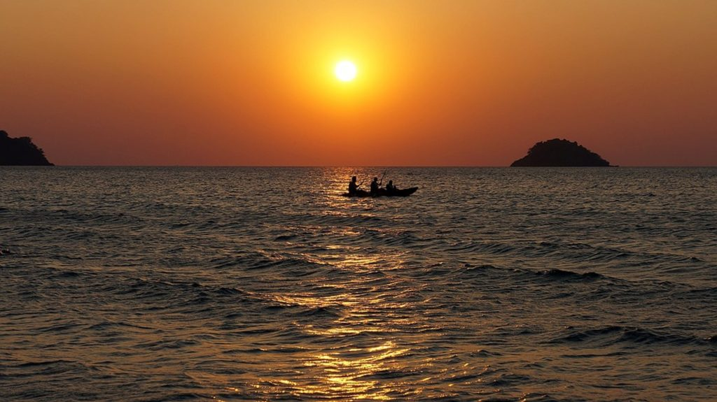 a small canoe carrying three people on the water.  SUn is  ayellow ball in an orage sky. calm ocean waters.  a very tiny hill of land way foff in the distance.