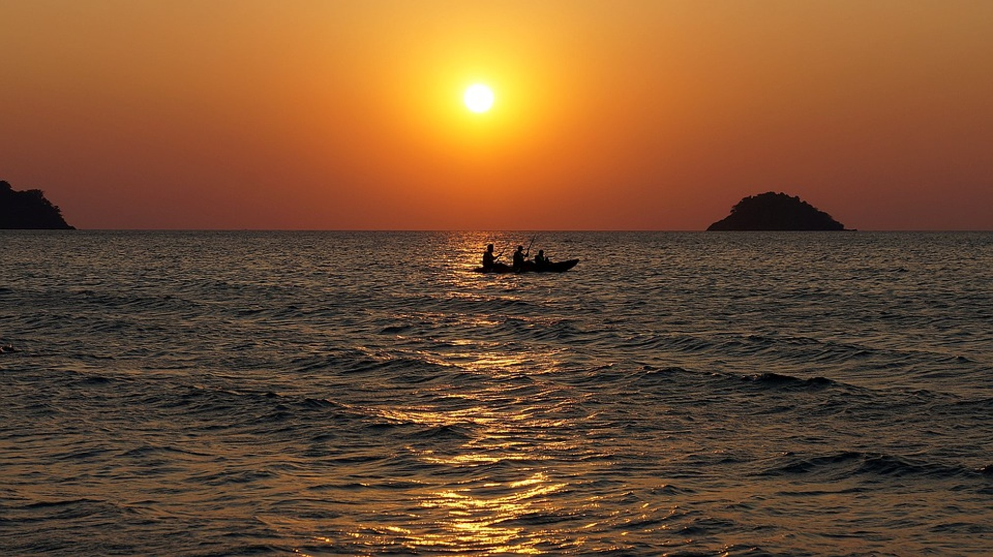 small boat with thtree people on a peacful ocean at nearly sundaown. Orange sky very low golden sun