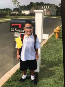 Michael as a littel kindergartener, standing at the mailbox on his first day of school smiling big!