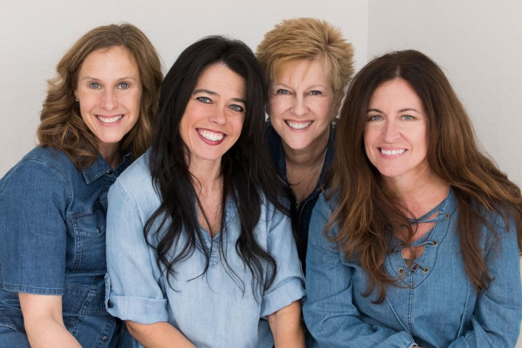 The 4 chicks sitting and smiling all in denim blue