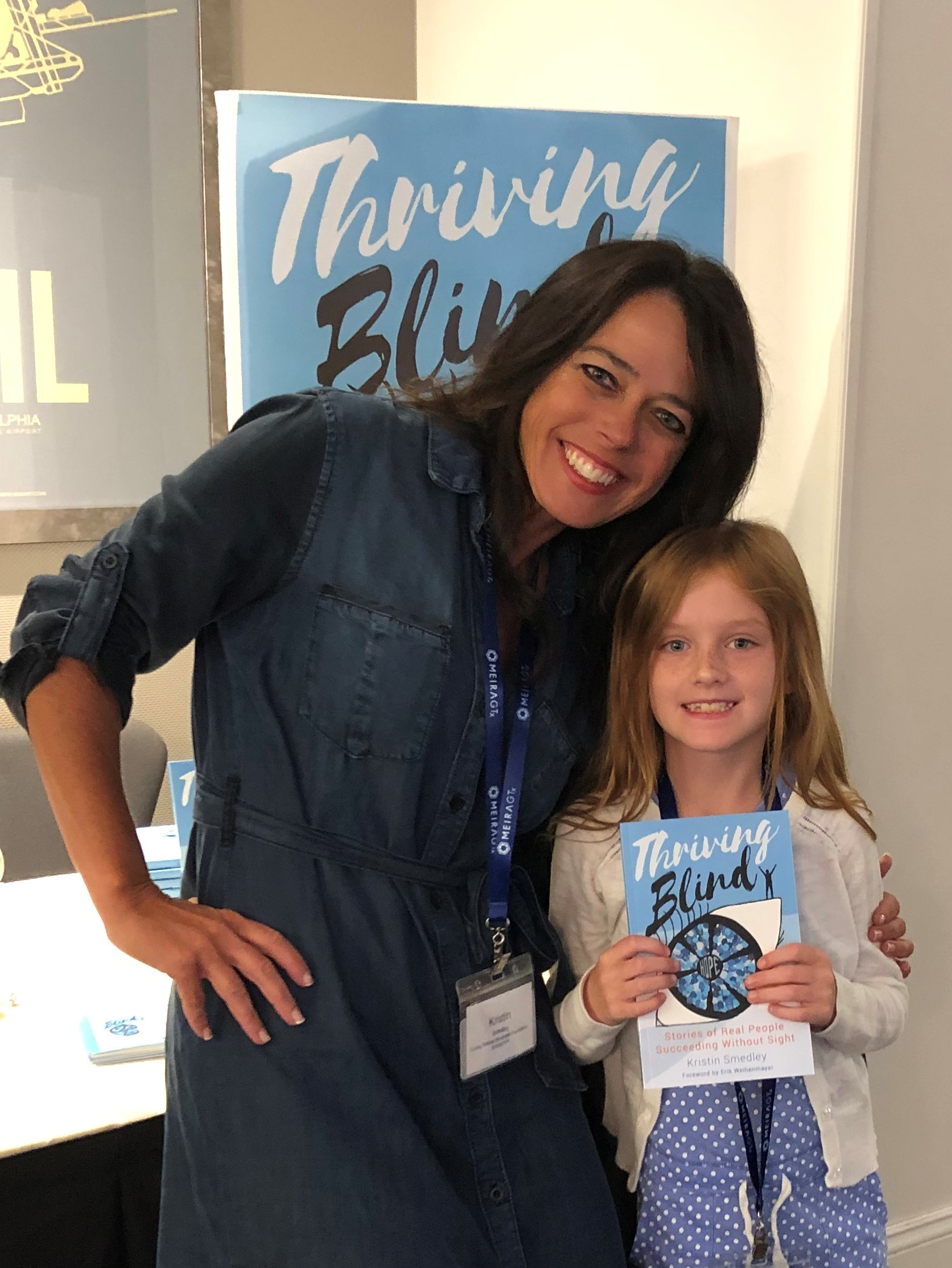 Kristin and a thrid grade girl holding the book thriving blind